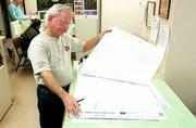 Gene Shaughnessy, Lawrence's chief building inspector, examines building plans at city hall. Inspectors issued permits for $175 million in construction last year, a city record.