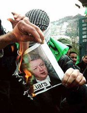 Supporters of the Islamic group Hamas burn photos of President Clinton and Israeli Prime Minister Ehud Barak during a demonstration Friday in the West Bank town of Nablus.