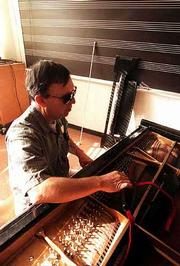 Loren Buntemeyer, the only piano technician at Kansas University, cares for more than 130 pianos. His blindness is no handicap to his precision work.