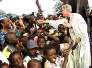 Clinton receives an enthusiastic welcome from the people of the Nigerian village of Ushafa on Aug. 27, 2000. Clinton is wearing a babariga, a Nigerian garment reserved for royalty, given him by the local chief.