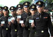 Thai soldiers wait in line with ID cards to vote in Bangkok. Voters in Thailand's general election Saturday were choosing between a longtime leader who has failed to pull the country out of economic crisis and a favored but tainted tycoon promising renewed prosperity.