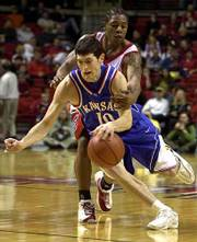KU's Kirk Hinrich, front, drives past Texas Tech's Jamal Brown. Hinrich had 13 points and five assists, while Brown had 23 points and nine assists in the Jayhawks' 94-82 victory on Saturday in Lubbock, Texas.