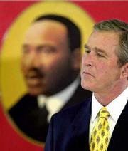 President-elect George W. Bush listens to a speech during a Martin Luther King Jr. holiday event. On Monday Bush was at Kelso Elementary School in Houston.