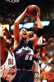Utah center Greg Ostertag (00), seen here playing against the Houston Rockets, has smoothed things over with Jazz coach Jerry Sloan. Ostertag, a former Kansas University player, on Monday withdrew his request to be traded following an incident near the end of Saturday's game in Salt Lake City.