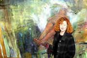 """Judith McCrea stands beside one of her paintings, which she describes as having an """"apocalyptic, mystical sense."""" McCrea is among Kansas University faculty who are showing their works through Feb. 2 in the Art and Design Gallery at KU."""