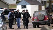 Law enforcement officials line the entrance to the Coachlight Motel and R.V. Park near Woodland Park, Colo. Acting on a tip, authorities Monday captured four of the seven convicts who broke out of a Texas prison nearly six weeks ago and allegedly gunned down a policeman on Christmas Eve. A fifth inmate killed himself at the park.