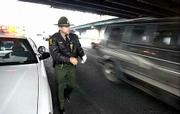 Illinois State Police trooper Javier Martinez keeps a cautious eye on passing traffic as he makes a traffic stop. Drivers seem to be paying less respect to law enforcement and emergency workers on the road.