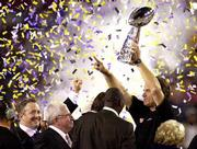 Baltimore coach Brian Billick hoists the Vince Lombardi trophy following the Ravens' victory over the New York Giants in Super Bowl XXXV. The Ravens won, 34-7, Sunday at Tampa, Fla. Ravens owner Art Modell is second from left.