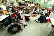 The Lawrence school district adheres to a policy of inclusion that insures that students with disabilities are integrated into classrooms with their nondisabled peers. Here, Deerfield fourth-grader Brett Stanclift's wheelchair sits empty as he and his classmates in Karen Warner's class spread out in a circle on the classroom floor. Brett and his classmates were passing around a corn snake.