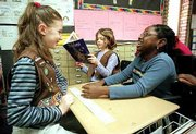 Inclusion extends to all grade levels in the Lawrence school district. Helen Somiari, a Deerfield third-grader who uses a wheelchair, right, is read to Sarah Hanson, left, and Pamina Buechner, center.