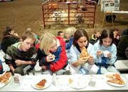 "A group of Deerfield Elementary School fourth-graders enjoys a pizza made from ingredients from beef and dairy cows, vegetables and grains. Hundreds of Lawrence schoolchildren experienced some lessons on the meaning of agriculture in their lives during the ""Slice of Agriculture"" program Monday at the Douglas County 4-H fairgrounds. From left are Taylor Stuart, Taeler King, Jessica Aranda and Apollonia Shreders."