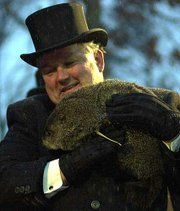 Weather-prognosticating groundhog Punxsutawney Phil is held by handler Bill Deeley.