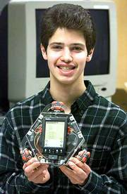 Computer science student Grigoriy Reshko shows a Palm Pilot-controlled robot that he helped develop at Carnegie Mellon University's lab. Free software enables the three-wheeled robot to follow a wall or roam a room for hours, making turns whenever it nears a wall or furniture, as well as twirl in circle.