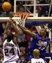 PHILADELPHIA'S THEO RATLIFF, right, blocks a shot by New Jersey's Stephen Jackson. The Nets won, 96-89, on Sunday at East Rutherford, N.J.