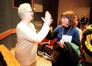 Molly Ivins, political columnist and author, is the recipient of this year's William Allen White Foundation national citation, an award for excellence in journalism. Ivins, left, high-fives Julia Rholes, Kansas University's interim dean of libraries, when they realized they attended the same junior high school in Texas. Ivins spoke Friday at KU's Woodruff Auditorium.