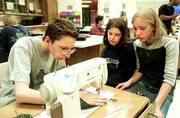 Mitchell Clark, left, South Junior High School seventh-grader, works on a class project in his home economics class while classmates Kaylee Flory, center, and Mary Cottrell wait their turn at the sewing machine.
