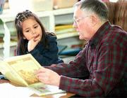 East Heights School kindergartner Lacoya Cloud enjoys her weekly reading session with volunteer Lawrence Penny of the Lawrence Breakfast Optimists. Penny and other readers visit children each Tuesday to read to them during lunch time.