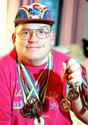 An accomplished Special Olympian, Ottawa resident Chuck Crawford travels today to Anchorage, Alaska, for the 2001 World Winter Games. Crawford is shown at home Thursday with a few of his medals, including his four gold medals for cross-country skiing, the event in which he will compete in Alaska.
