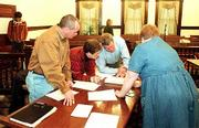 The candidate field for the April 3 Lawrence City Commission general election is settled. Serving as vote canvassers, at foreground from left, County Commissioner Jere McElhaney, Register of Deeds Sue Neustifter and County Commissioner Charles Jones, inspect ballots Friday. At far left is city commission candidate Adam Mansfield, who picked up 14 votes in the canvass, giving him the last of six spots on the April ballot.