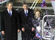 Nancy Reagan christens the nuclear aircraft carrier USS Ronald Reagan as President Bush, left, and Newport News Shipbuilding Chief Executive Officer William Fricks, center, look on. The ship was christened Sunday in Newport News, Va.
