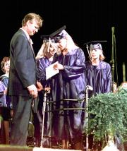 FORMER Heath High School principal Bill Bond, left, and Mandy Jenkins, second from left, watch as Heath High School shooting victim Missy Jenkins, who is partially paralyzed, walks off stage at graduation June 2, 2000, in Paducah, Ky. Bond, now a safety expert with the National Association of Secondary School Principals, learned about student silence firsthand.