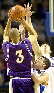 Kansas State's Quentin Buchanan (3) launches a shot over KU's Brett Ballard, center, and Nick Collison.