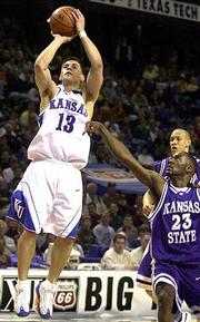 Jeff Boschee (13) launches a shot for Kansas over Phineas Atchison (23) of Kansas State. Boschee scored 23 points Friday in KU's Big 12 quarterfinal victory at Kansas City, Mo.