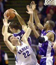 Jeff Carey fights for a rebound with KSU's Ivan Sulic, rear, and Travis Reynolds, right.