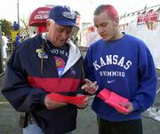 Before the start of Kansas University's Big 12 Tournament game Friday evening against Kansas State, KU swimmers and divers were on hand at the KU Alumni Association's tent at Kemper Arena to pass out fliers announcing a protest this morning on the KU campus. George Schluter, Kansas City, Mo., a 1961 KU graduate, left, listens to sophomore swimmer Cory Gallagher explain the loss of the men's swimming and tennis programs. Schluter, an official at KU swim meets since the mid-1980s, said he was saddened by the cuts and how they took place.