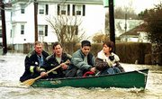 Cranston, R.I., firefighters, in back of canoe, rescue Robert Rosa, second from right, and Vica Rhaney, right, from their house Thursday. The river behind their house overflowed into the street after continuous heavy rains.