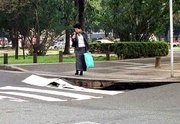 Southwestern Japan is coping in the aftermath of a magnitude-6.4 earthquake. Here, an unidentified woman checks out a caved-in street Saturday in Hiroshima. The earthquake damaged water pipes, delayed trains and left at least two people dead.