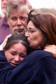 Dalas Kaelin, 16, left, is hugged by her mother, Susie Kaelin in the park across the street from Granite Hills High School after a shooting Thursday. Dalas' father, John Kaelin, looks on. The shooting was the school district's second incidence of violence in two weeks.