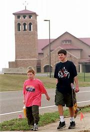 The bell in the tower at Corpus Christi Catholic Church, 6001 W. 15th Street, rings at 6 every morning, and some neighbors don't appreciate the early wake-up call. Friday, Tyler Kincaid, 10, Lawrence, left, and Chris Bell, 12, Fayetteville, Ark., walked through the neighborhood near the Corpus Christi campus.
