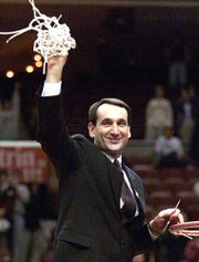 Duke coach Mike Krzyzewski holds up the net that was cut after Duke won the NCAA East Regional title. The Blue Devils downed USC, 79-69, on Saturday in Philadelphia.