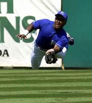 Kansas City's Trenidad Hubbard makes a diving catch of a ball hit by Atlanta's Pedro Swann. The Royals beat the Braves on Saturday at Haines City, Fla.