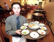 Jin Won, manager of Murra Cafe, shows off whae-dup-bop, a dish of raw Red Snapper, radishes, lettuce, carrots and cucumber.