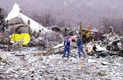 Investigators walk through the scene of a plane crash Friday near the Aspen-Pitkin County Airport in Aspen, Colo. Eighteen people were killed when the plane crashed while landing Thursday night.