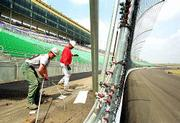 International Speedway Corp. will take possession of the Kansas Speedway on Sunday, in time to spruce it up for its first auto race June 2. Christopher Dean, left, and David Myers, workmen for George J. Shaw Co. of Kansas City, Mo., clean up some leftover sections of fence Friday near the finish line at the speedway in Kansas City, Kan.