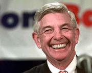 Hugh McColl, then CEO of NationsBank, smiles during a news conference announcing the multibillion dollar merger of NationsBank and Bank of America. Since the 1998 merger, Bank of America shareholders have lost almost half their investment, while McColl will retire April 25 with a $2 million-a-year pension.