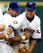 Texas Rangers Ken Caminiti, left, and Alex Rodriguez celebrate their victory over Anaheim. The Rangers won their home opener 3-2 on Tuesday at Arlington, Texas.