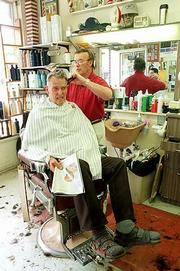 Richard League, Lawrence, believes time spent getting a haircut can lead to good conversations about local politics. Wednesday at Amyx Barber Shop, 842-1/2 Mass., League, seated, and barber Mike Amyx, a former mayor and county commissioner, talk politics a day after local elections.