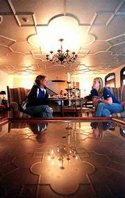 In a newly refurbished living room, Chi Omega members Dana McJunkin, left, and Michelle Guerry talk about the remodeled atmosphere. Their sorority and Theis Doolittle Associates received the Award for Excellence from the Kansas Preservation Alliance for the rehabilitation of the house.