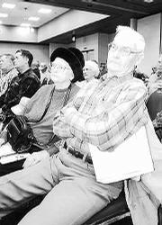 Richard Postma, right, 1012 N. 600 Road in Baldwin, listens to bankruptcy attorneys talk about the status of the Farmers Cooperative Assn. at a January meeting.