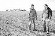 After a colder-than-usual winter, Steve Wintermantel, left, and his brother Mike walk across a field that received a welcomed amount of moisture after a dry 2000.