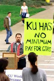Helmut Tweer, a graduate teaching assistant in Kansas University's German language department, talks about the importance of GTAs and how they are compensated during a lunch hour rally Thursday on Wescoe Beach. The GTAs are in the process of negotiating their second contract since they unionized in 1995.