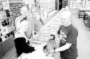 At Love Garden Sounds, 936 1/2 Mass., fans of cats and used CDs can get what they want. Gathered around the store's original cat, Jack, are, employees, from back left, Debby Vanderwall, Kelly Corcoran and Emily Hadley. At right is owner Kory Willis.