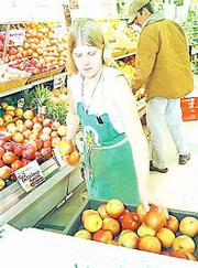 """The USDA passed regulations recently that require organic farmers to meet certain standards to carry an """"organic"""" label. In January at the Community Mercantile Co-op, 901 Miss., produce assistant Bridget Meier stocks organically grown apples."""