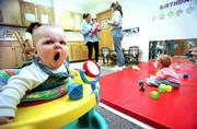 The Kansas Department of Social and Rehabilitation Services is pushing a program that can help low-income parents who remain in the work force pay for day-care expenses. Thursday, 8-month-old Emma Pravecek stretches her face with a yawn at the Children's Learning Center, 205 N. Mich.