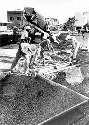 "As long as there&squot;s been a downtown, there&squot;s been an issue with parking whether it was horses, buggies or, later, cars. Workers in the early 1970s pour concrete to form the ""saw-tooth"" parking spaces that line Massachusetts Street."