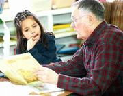 East Heights School kindergartner Lacoya Cloud enjoys her weekly reading session with volunteer Lawrence Penny, a member of the Lawrence Breakfast Optimists. Penny and other readers visit the same children every Tuesday to read to them during lunch.